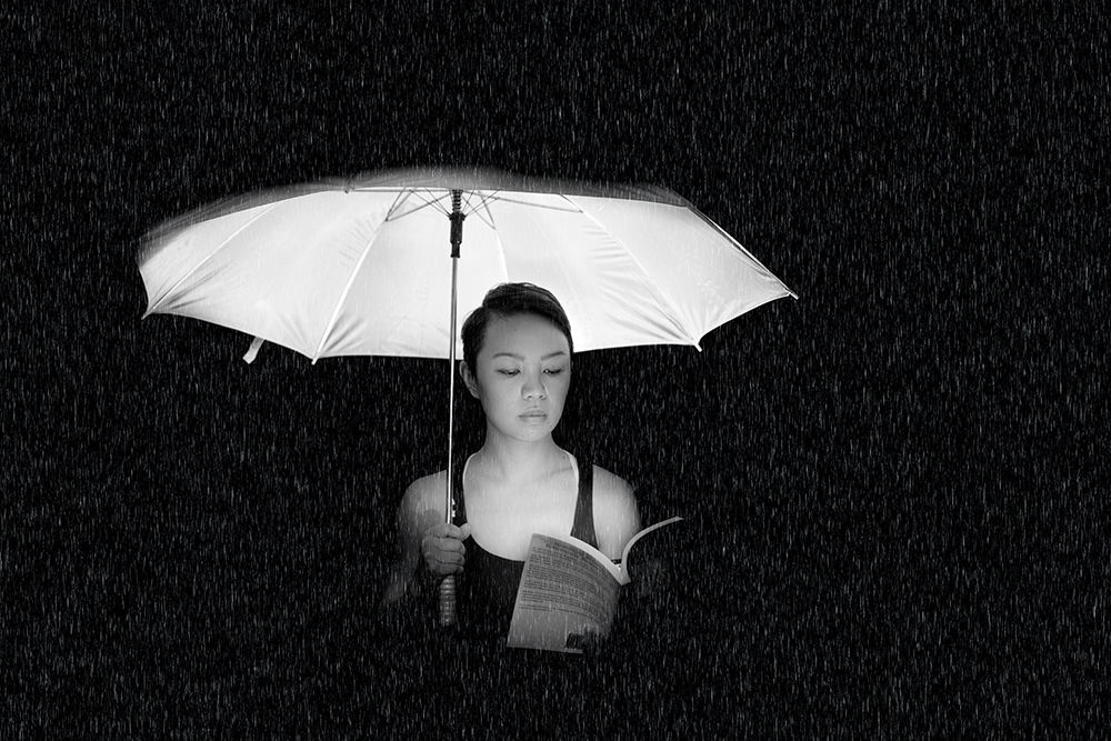 Black and white image of woman holding umbrella lit from below with a book