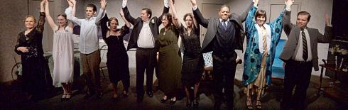 Cast of play with raised linked hands in the air