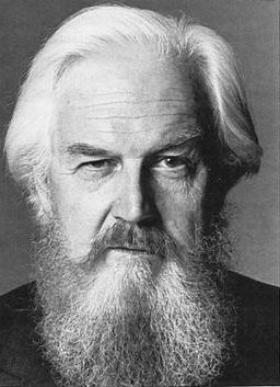 Older man with white hair and a long beard giving a skeptical expression.