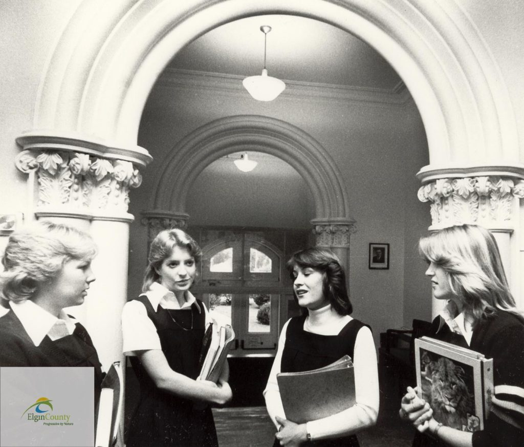 Black and white photo of women under a rotunda holding books