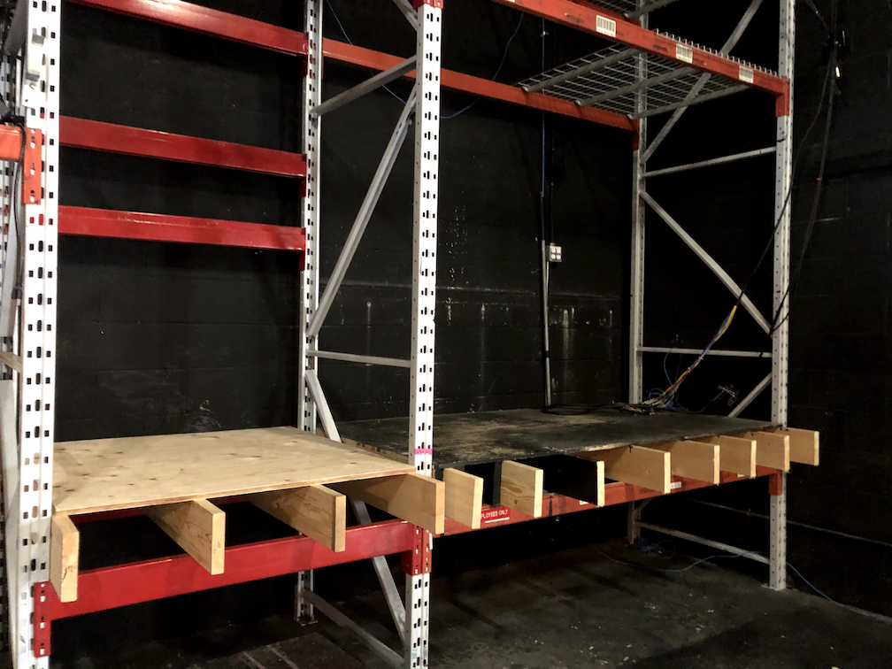 A photo of the new booth under construction. The floor is being constructed with plywood on top of dimensional lumber, and set into a metal framework.